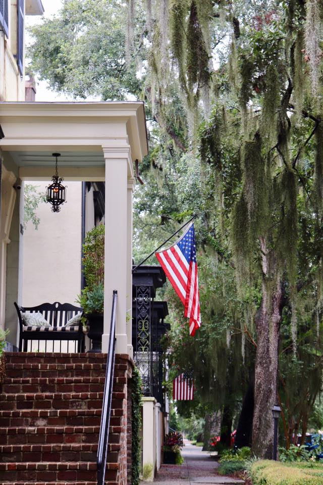 Side view of historic row house in Savannah, GA with brick steps, black bench, and American flag hanging from the front.