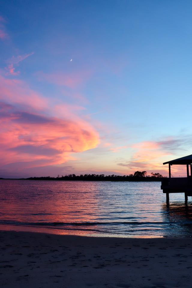 Sunset over Tybee Island, GA beach with pink swirling clouds and blue sky