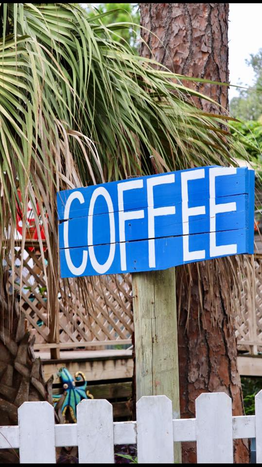 Blue painted wooden sign with white letters reading COFFEE from Tybean Coffee shop on Tybee Island, GA.