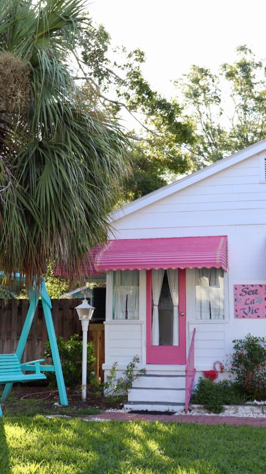 White beach bungalow with pink awning and pink door located on Tybee Island, GA